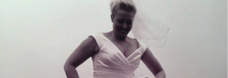Tha happy bride wearing wedding dress and wellingtons