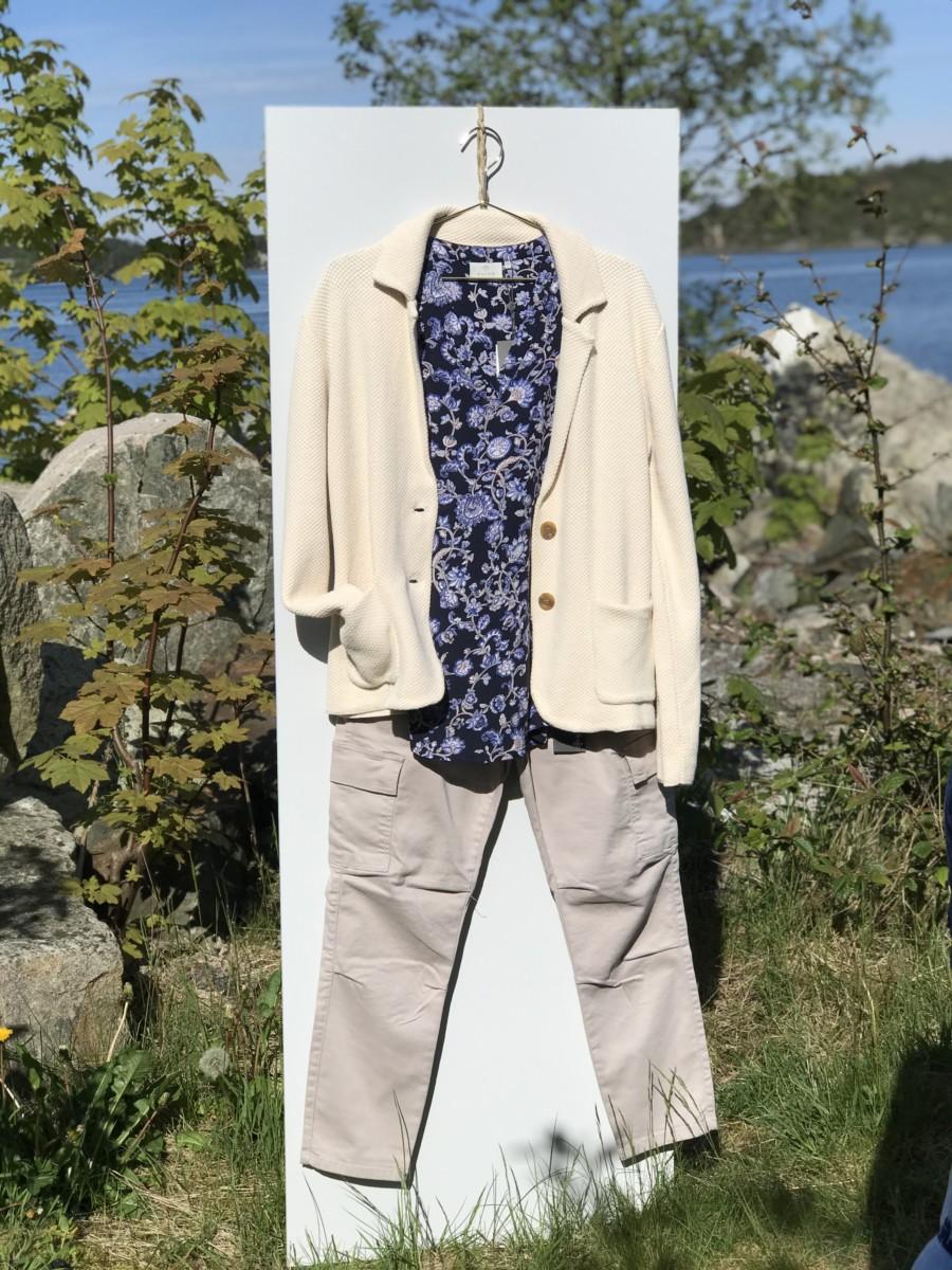 Lys sandfarget bukse med kremfarget jakke og mørk blå topp
